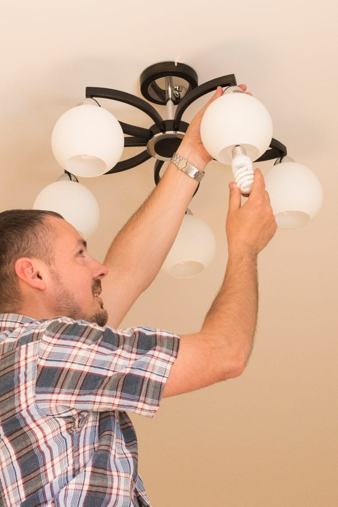 man changing lightbulb to add value to home during covid